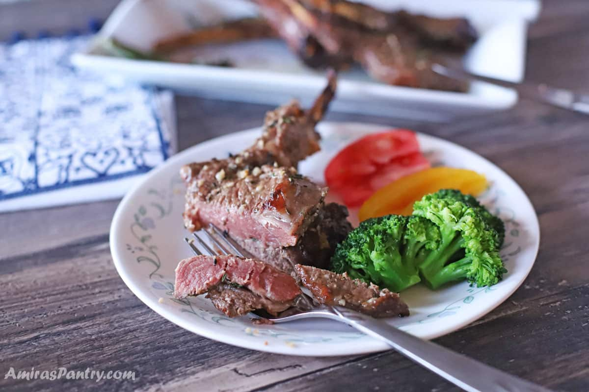 Lamb chopped cut on a white plate with veggies on the side.