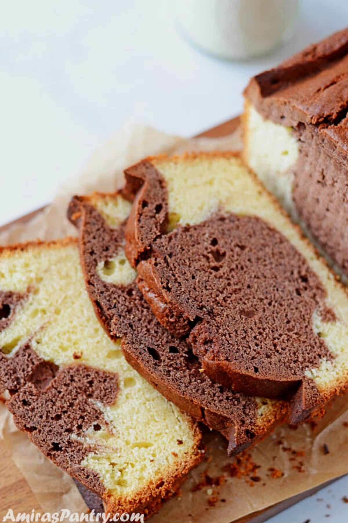 Sliced marble pound cake on a wooden board with a bottle of milk in the back.