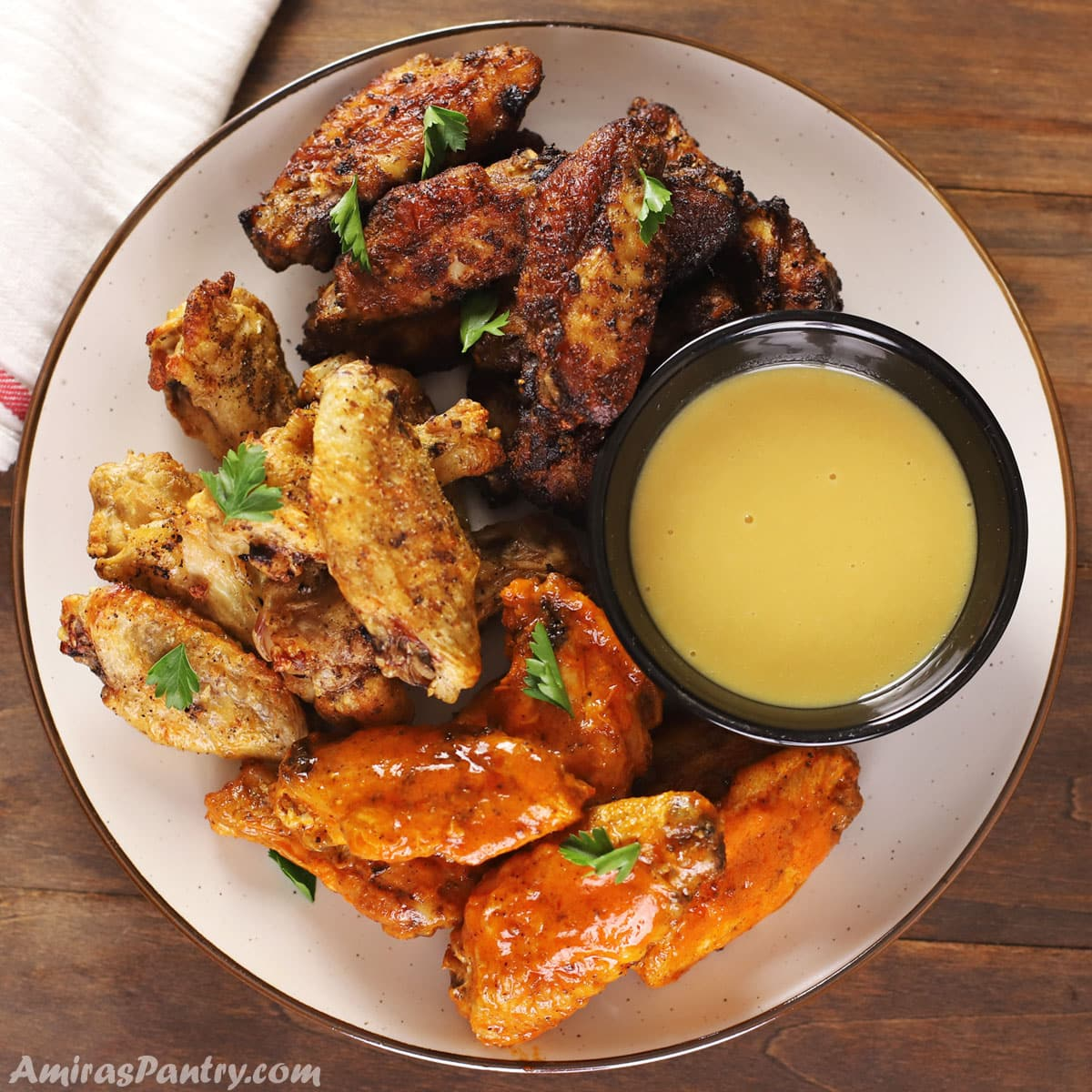 A serving plate of different trypes of air fried wings with a small bowl of sauce on the side.