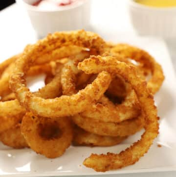 A close up photo of air fried onion rings on a white plate.