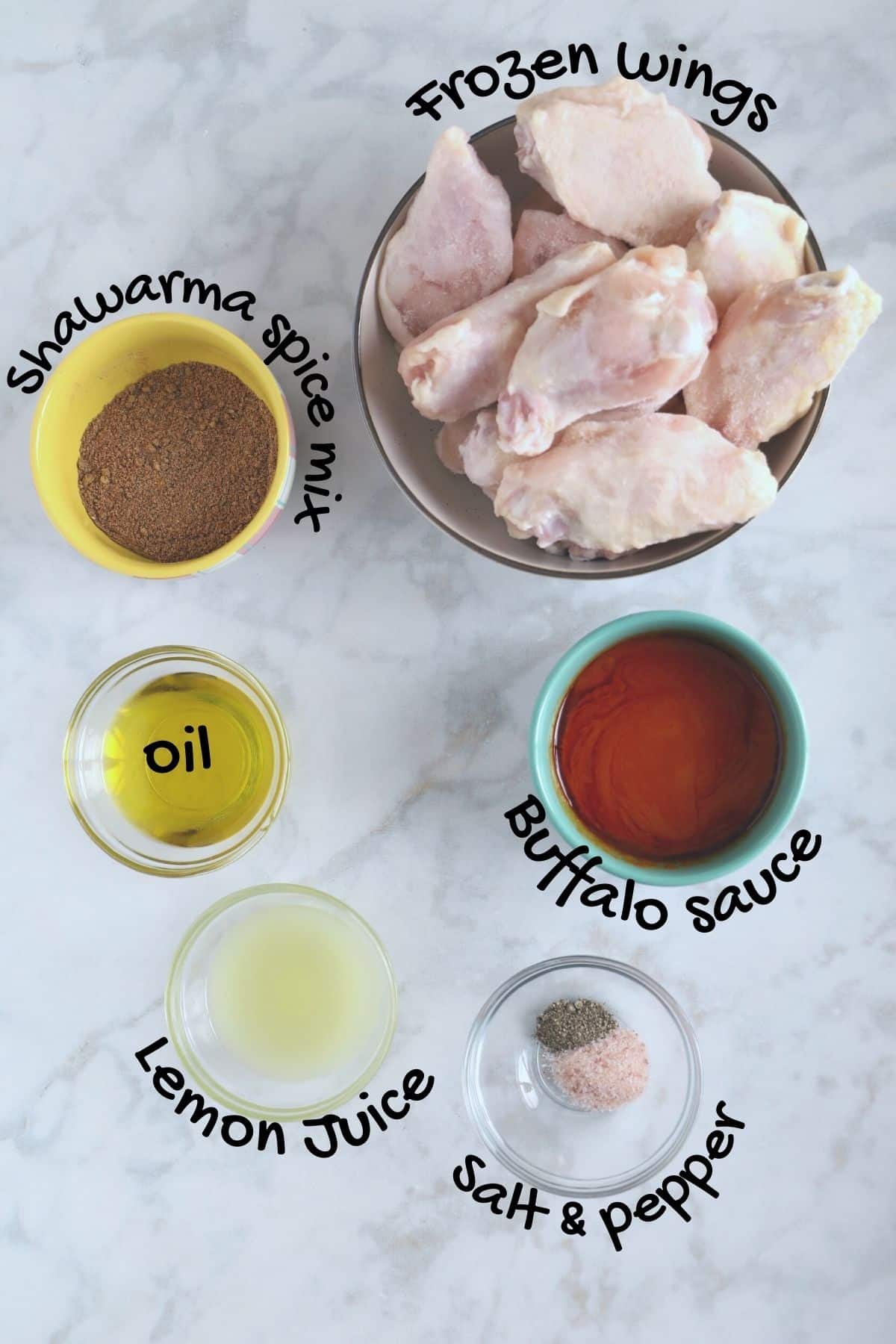 Air fryer chicken wings ingredients placed on a white surface.