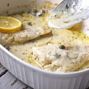 A spoon scooping some creamy sauce over baked fish lemon in a white pan.