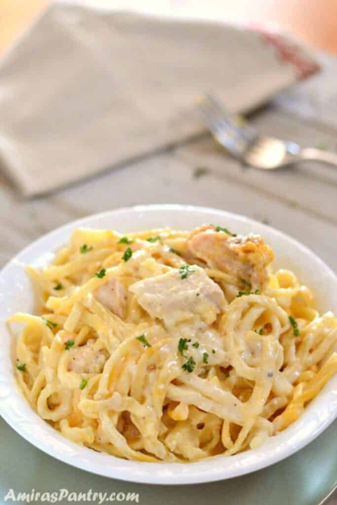 A white plate with some chicken tetrazzini and a fork in the back.