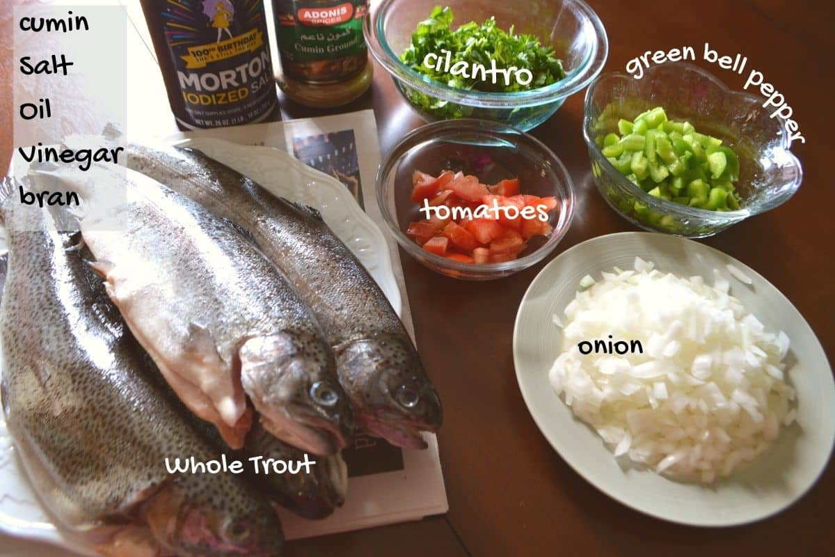 Grilled trout ingredients placed on a wooden surface.