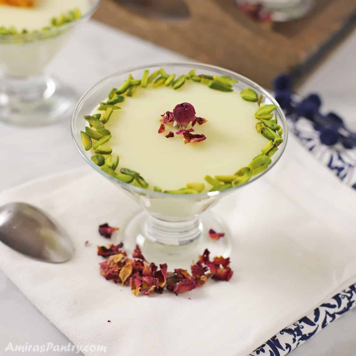 A dessert bowl of mahalabia garnished with pistachios and edible roses placed on a white towel.