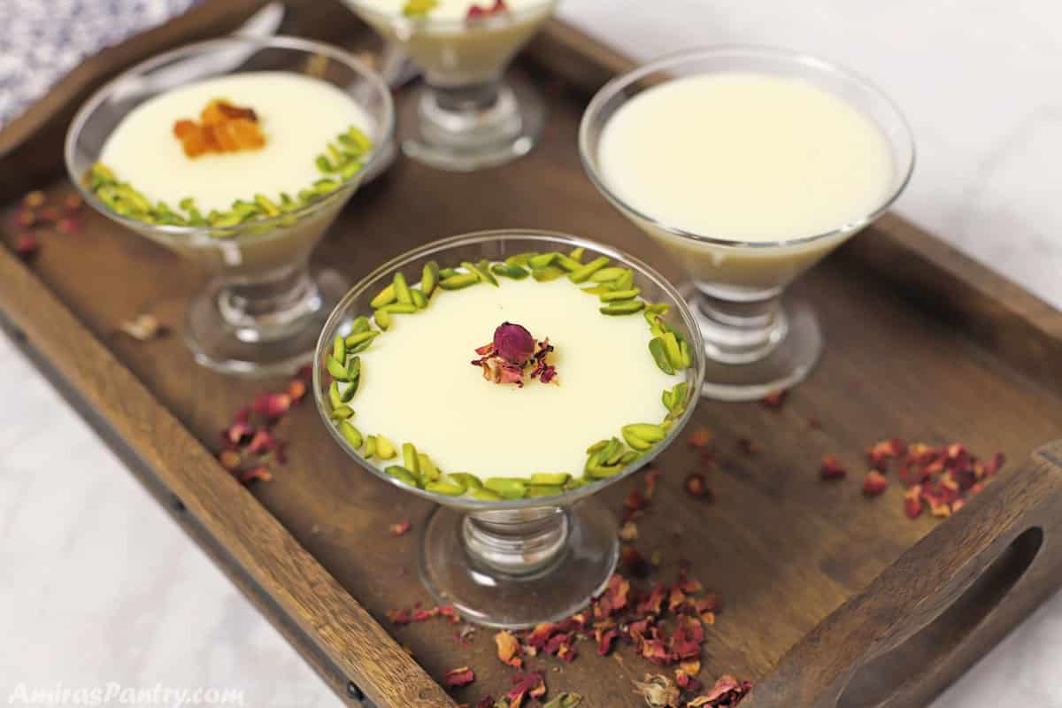 4 glass cups of milk pudding placed on a dark brown wooden tray.