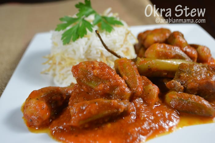 Okra stew in a white plate with rice in the back.