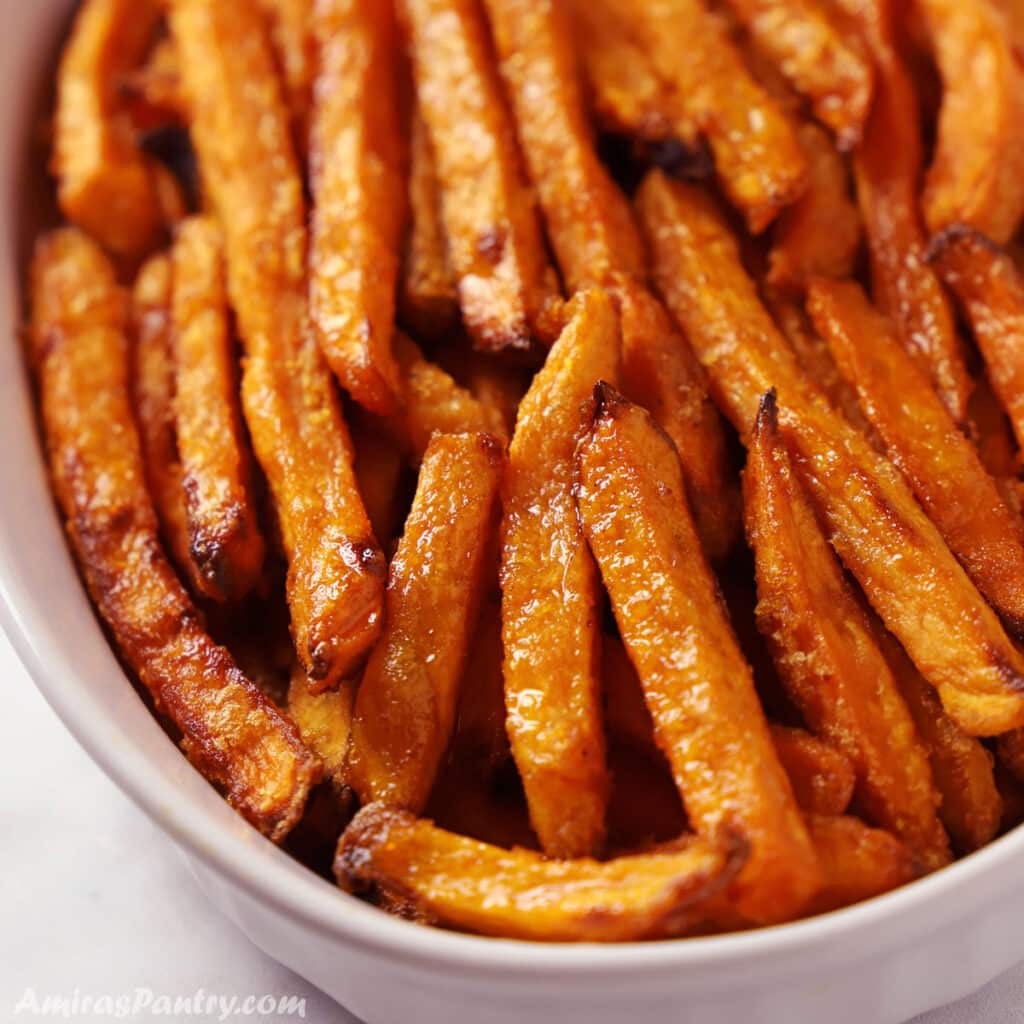A close up look on a white serving plate with sweet potato fries.