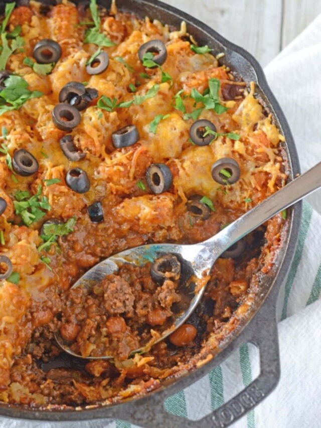 A bird's eye image of a taco tater tot casserole with a spoon in it.
