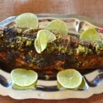 A grilled trout on a silver serving platter with lemon rinds.