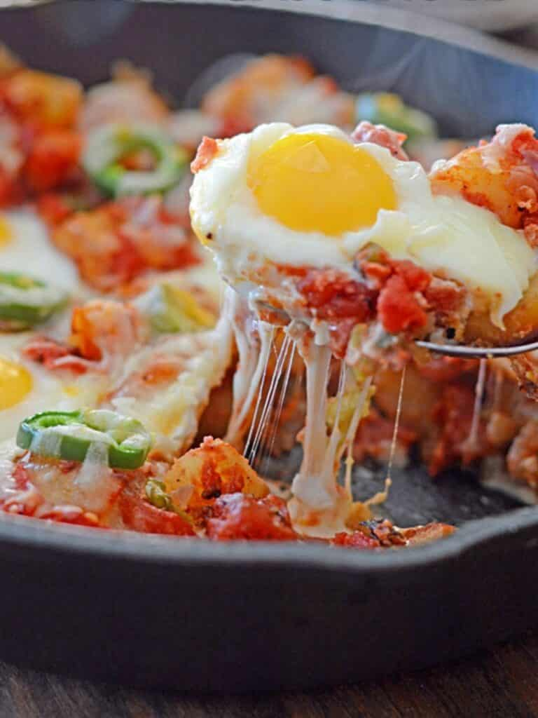 A spoon scooping and egg from the potato shakshuka with cheese.