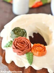 A top view of pumpkin bundt cake on a white platter with a bottle of milk in the back.