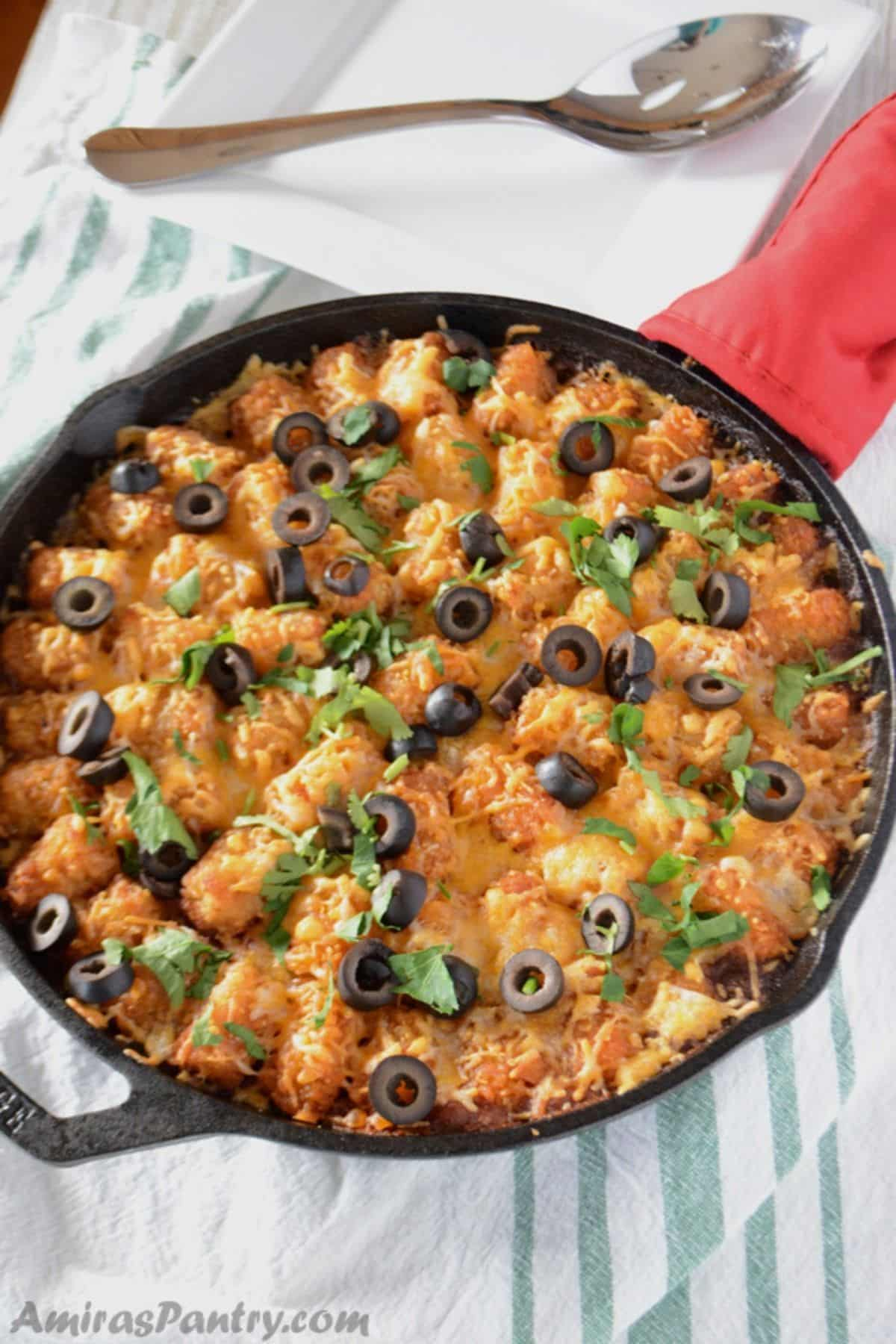 A pan with Tater tots, cheese and olives
