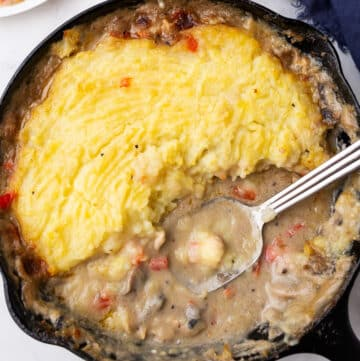A bird's eye view of a cast iron skillet with chicken and mashed potatoes with a spoon in it.