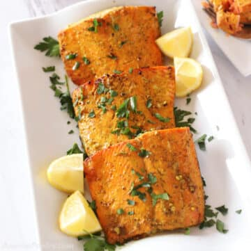 Air fried salmon pieces on a white platter garnished with lemon wedges and parsley.