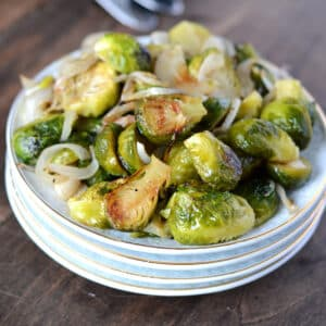 A close up image of roasted Brussels sprouts on a stack of white dishes.
