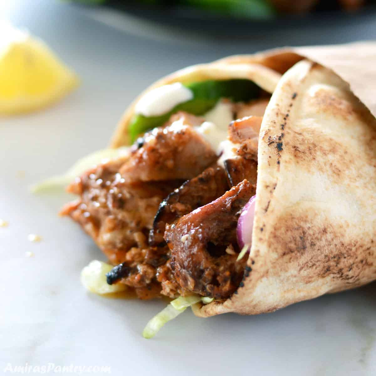 A close up picture of a chicken shawarma wrap placed on a awhite countertop with a lemon wedge on the side.