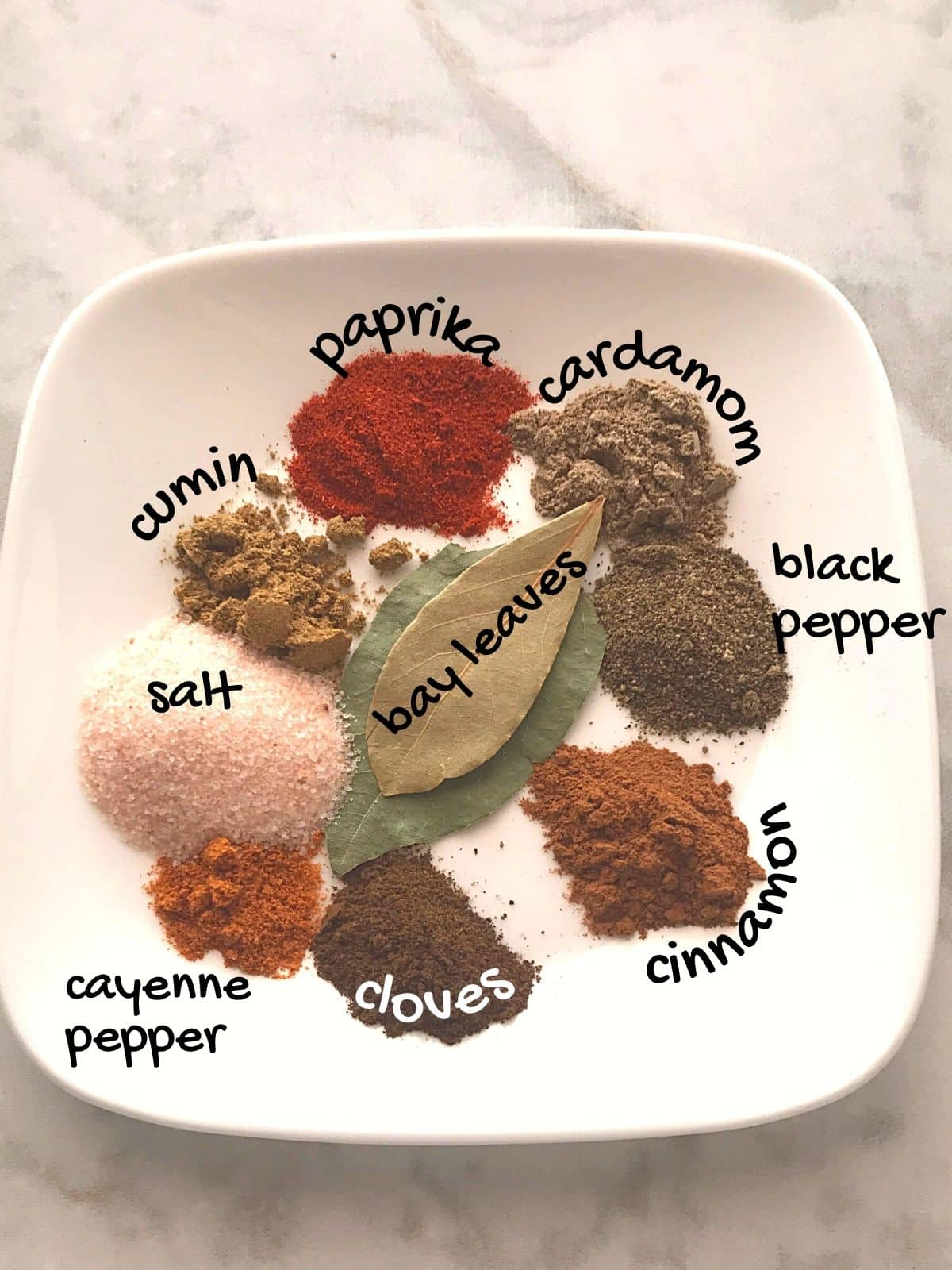 A white plate with shawarma spice blend ingredients placed on a white marble surface.
